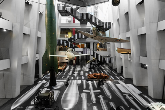 """Full view of the IWM London's atrium, where Ai Weiwei's """"History of Bombs"""" is on display using printed Harlequin Clarity vinyl floor"""