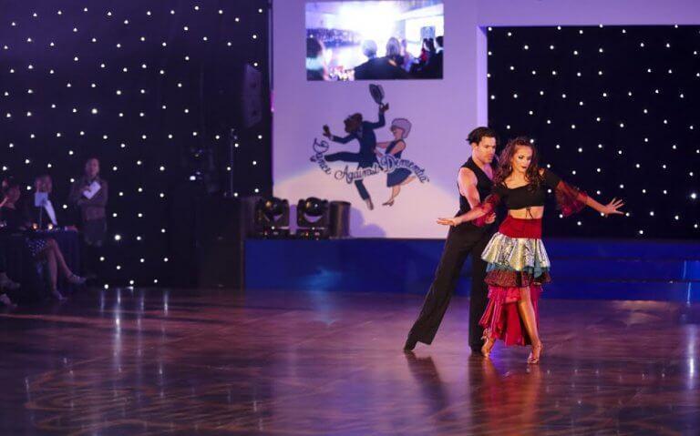 Ballroom dancers performing on Harlequin dance floor