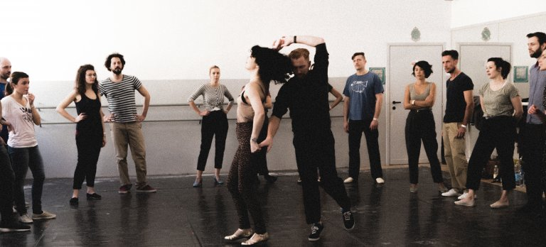 A group of people surrounding two swing dancers