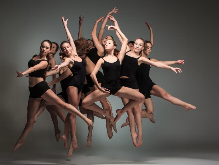 Jazz dancers jumping in front of a grey backdrop