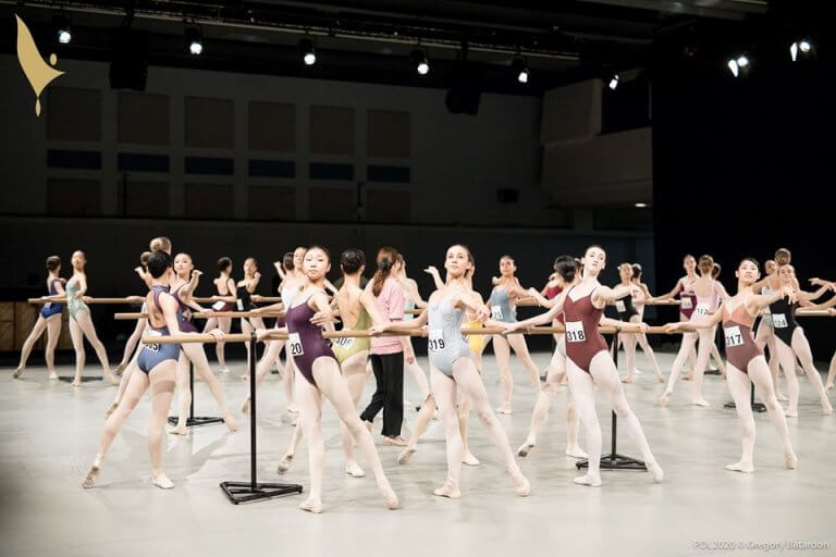 Young ballerinas warming up at the barre during the competition
