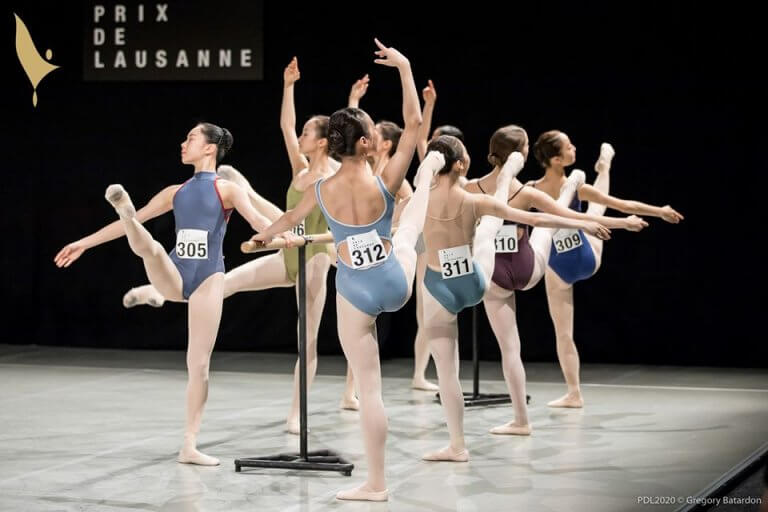 Ballerinas at the barre, with their competition numbers attached to their bodysuits
